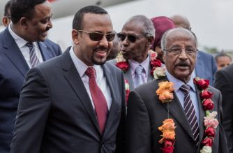 Eritrea's Foreign Minister Osman Saleh Mohammed (R) walks with Ethiopia's Prime Minister Abiy Ahmed (2L) and Ethiopia's foreign minister Workeneh Gebeyehu (L) as an Eritrean delegation for peace talks with Ethiopia arrives at the international airport in Addis Ababa on June 26, 2018.  An Eritrean delegation has made a rare visit to the Ethiopian capital, taking the next step in a historic diplomatic ballet aimed at ending decades of conflict and hostility. The thaw between the foes who fought a bitter border war 20 years ago comes after an olive branch was dramatically offered by new Ethiopian prime minister, Abiy Ahmed.  / AFP PHOTO / YONAS TADESSE