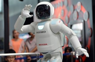(FILES) This picture taken on July 3, 2013 shows Honda Motor's humanoid robot Asimo interacting with visitors at the National Museum of Emerging Science and Innovation in Tokyo on July 3, 2013.  Launched in 2000, the humanoid machine resembling a shrunken spaceman has become arguably Japan's most famous robot, wheeled out to impress visiting politicians over the years. / AFP PHOTO / YOSHIKAZU TSUNO