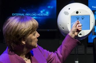 """(FILES) In this file photo taken on April 25, 2018, German Chancellor Angela Merkel interacts with a CIMON (Crew Interactive Mobile CompanioN) unit, a mobile and autonomous assistance system designed to aid astronauts with their everyday tasks on the International Space Station, at the ILA Berlin International Aerospace Exhibition at Schoenefeld airport near Berlin.  A floating, ball-shaped, artificial intelligence robot, specially trained to follow around a German astronaut at the International Space Station, is scheduled to blast off Friday, June 29, 2018 on its ground-breaking mission. The basketball-sized device called CIMON -- shortened from Crew Interactive MObile CompanioN -- was described as a """"flying brain"""" by Manfred Jaumann, head of microgravity payloads at Airbus.  / AFP PHOTO / John MACDOUGALL"""