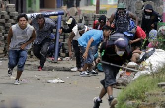 Anti-government demonstrators take cover behind a barricade, during clashes with riot police and members of the Sandinista youth, in Masaya some 35 km from Managua on June 19, 2018. / AFP Photo / Inti Ocon