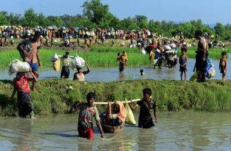 (FILES) In this file photo taken on October 16, 2017 Rohingya refugees carry a woman over a canal after crossing the Naf River as they flee violence in Myanmar to reach Bangladesh in Palongkhali near Ukhia.  / AFP Photo / Munir Uz Zaman