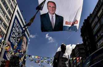 A man walks past banners of Turkey's main opposition party presidential candidate Muharrem Ince (top) and Turkish President Recep Tayyip Erdogan (L) in Istanbul on June 20, 2018. / AFP Photo / Aris Messinis