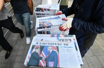 A South Korean newspaper deliveryman collects newspapers in Seoul reporting the summit between US President Donald Trump and North Korean leader Kim Jong Un on June 12, 2018. AFP Photo / Jung Yeon-je