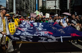 Protesters carry a banner as they attend a march in Hong Kong on July 1, 2018, to coincide with the 21st anniversary of the city's handover from British to Chinese rule. / AFP PHOTO / Philip FONG