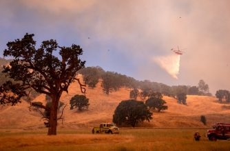 A helicopter drops water on a hillside as firefighters scramble to get control as flames from the Pawnee fire near Clearlake Oaks, California on July 1, 2018.  More than 30,000 acres have burned in multiple fires throughout the region.  / AFP PHOTO / JOSH EDELSON