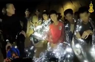 "This handout video grab taken from footage released by the Royal Thai Navy on July 4, 2018 and taken on July 3 shows members of a Thai youth football team (R), some wrapped in portective foil blankets, sitting with a diver (L) inside the Tham Luang cave in Khun Nam Nang Non Forest Park in Mae Sai district, Chiang Rai province. The new video released on July 4 filmed in the bowels of a northern Thai cave showed members of a trapped football team laughing as they greet the camera to say they are in good health after their astonishing discovery by divers. / AFP PHOTO / ROYAL THAI NAVY / Handout / -----EDITORS NOTE --- RESTRICTED TO EDITORIAL USE - MANDATORY CREDIT ""AFP PHOTO / ROYAL THAI NAVY"" - NO MARKETING - NO ADVERTISING CAMPAIGNS - DISTRIBUTED AS A SERVICE TO CLIENTS"