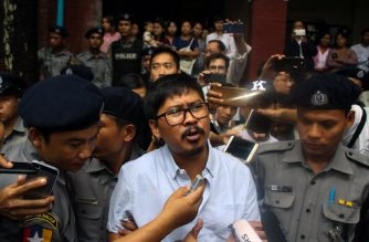 Detained Myanmar journalist Wa Lone (C) speaks to reporters as he is escorted by police from a courthouse following his ongoing pre-trial hearing in Yangon on July 9, 2018. / AFP Photo / Myo Kyaw Soe