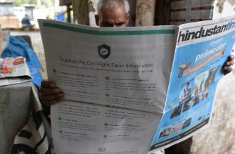 This photo illustration shows an Indian newspaper vendor reading a newspaper with a full back page advertisement from WhatsApp intended to counter fake information, in New Delhi on July 10, 2018.  / AFP Photo / Prakash Singh