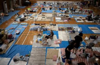 People affected by the recent flooding rest at a makeshift shelter in Mabi, Okayama prefecture on July 11, 2018. / AFP Photo / Martin Bureau