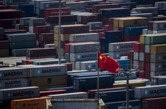 (FILES) This file picture taken on April 9, 2018 shows a Chinese flag in front of containers at the Yangshan Deep-Water Port, an automated cargo wharf, in Shanghai. China's surplus with the US swelled in June, data showed on July 13, 2018, likely stoking tensions with Donald Trump, who has imposed tariffs on billions of dollars of Chinese goods citing unfair trade practices. / AFP PHOTO / JOHANNES EISELE