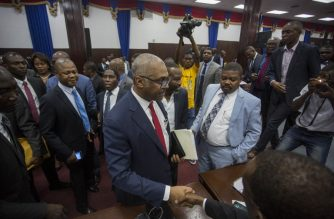 Prime Minister Jack Guy Lafontant greets supporters and opposition alike while leaving the assembly hall after announcing his resignation was accepted earlier in the day on July 14, 2018.   Haiti Prime Minister Jack Guy Lafontant is interpellated by 16 members of parliament after the recent riots on July 6,7,8, 2018 in Haiti following the increase in the price of fuel. / AFP PHOTO / Pierre Michel Jean