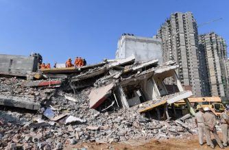 Members of the National Disaster Response Force (NDRF), along with local police, search for victims after an under construction building collapsed in the village of Shah Beri village in Greater Noida, a satellite town east of the Indian capital, in Uttar Pradesh on July 18, 2018. At least two people were killed and more were feared trapped after an under-construction building collapsed onto a residential complex outside Delhi, officials said on July 18. / AFP PHOTO / Prakash SINGH