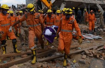 Members of the National Disaster Response Force (NDRF) carry out the body of a victim at the site of a collapsed building in the village of Shah Beri village in Greater Noida, a satellite town east of the Indian capital, in Uttar Pradesh on July 18, 2018. More than 100 Indian rescue workers were using steel cutters and drills on July 18 to try and free a dozen people feared trapped under the rubble of a collapsed six-storey building outside Delhi.  / AFP PHOTO / Prakash SINGH