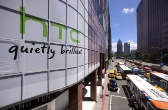 The logo for Taiwan's leading smartphone maker HTC (L) is pictured above a busy street in Taipei on July 20, 2012.  Taiwan's leading smartphone maker HTC said on July 19 it was suing technology giant Apple in the United States, claiming it has infringed o     AFP PHOTO / Sam YEH / AFP PHOTO