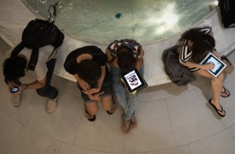 FILES: This picture taken on March 19, 2013 shows people using their smartphones and tablets in a shopping mall in Bangkok. A recent Facebook-sponsored study showed smartphone owners are often connected all day. People can be found glued to their smartphones at airports, on trains, in restaurants and even while walking on the street, creating a disconnection from their immediate surroundings. Smartphone sales are expected to continue to surge in 2013 with some 918 million units to be bought worldwide. AFP PHOTO/ Nicolas ASFOURI / AFP PHOTO / NICOLAS ASFOURI