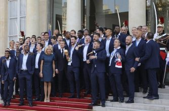 France's goalkeeper Hugo Lloris (C) holds the trophy next to France's coach Didier Deschamps (C, right) as French President Emmanuel Macron (C, left) and his wife Brigitte Macron welcome players and staff members of the French national football team after they won the Russia 2018 World Cup final football match during a reception at the Elysee Presidential Palace on July 16, 2018 in Paris.  / AFP Photo/ Ludovic Marin