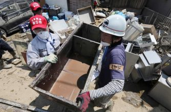 Volunteers remove items from a house in a flood-hit area in Kurashiki, Okayama prefecture on July 14, 2018. / AFP Photo / JIJI PRESS
