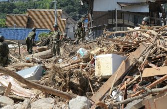 Member of Ground Self Defense Forces search for missing persons at a flood damage site in Kure, Hiroshima prefecture on July 12, 2018.  / AFP Photo / Jiji Press