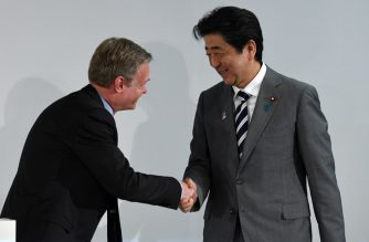 Japan's Prime Minister Shinzo Abe (R) shakes hands with French ambassador in Japan Laurent Pic (L) during a press conference in Tokyo to announce the 2018 Japonismes events in France, on July 2, 2018. / AFP Photo/ Martin Bureau