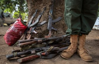 (FILES) A former child soldier stands next to rifles during the release ceremony for child soldiers in Yambio, South Sudan, on February 7, 2018. / AFP Photo / Stefanie Glinski