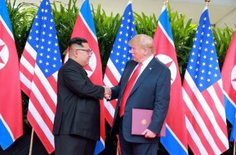 In this picture taken on June 12, 2018 and released from North Korea's official Korean Central News Agency (KCNA) on June 13, 2018, US President Donald Trump (R) and North Korea's leader Kim Jong Un (L) shake hands after signing documents at a signing ceremony during their historic US-North Korea summit, at the Capella Hotel on Sentosa island in Singapore. / AFP PHOTO / KCNA VIA KNS /
