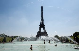 """(FILES) In this file photo taken on July 27, 2018 people cool themselves at the Trocadero Fountain in front of The Eiffel Tower in Paris, as a heatwave continues across northern Europe. Eiffel Tower workers are planning to strike this week over a new access policy for visitors which they say is generating """"monstruous"""" waits at the famous tourist landmark, union officials said on July 30, 2018. Since early July the monument has set aside half of daily tickets for people who buy them in advance on the internet and choose a scheduled time for their visit. / AFP PHOTO / Ludovic MARIN"""