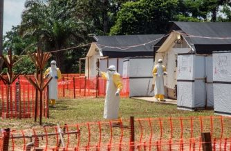 """(FILES) In this file photo taken on June 1, 2018 health workers operate within an Ebola safety zone in the Health Center in Iyonda, near Mbandaka. The Democratic Republic of Congo on August 1, 2018 reported an outbreak of Ebola in the east of the vast country, barely a week after it had declared the end to an outbreak in the northwest. """"At this point, there is no indication that these two epidemics, which are more than 2,500 kilometres (1,500 miles) apart, are connected,"""" Health Minister Oly Ilunga Kalenga said in a statement. / AFP PHOTO / Junior D. KANNAH"""