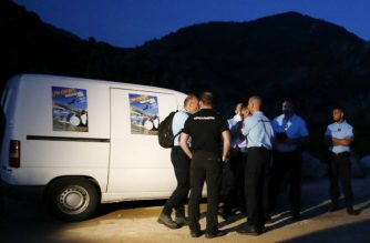 French Gendarmes stand next to a vehicle as they do searches at the canyon where four people died after a flood occurred due to bad weather conditions on August 1, 2018 close to the village of Soccia, on the French Mediterranean island of Corsica.  / AFP PHOTO / PASCAL POCHARD-CASABIANCA