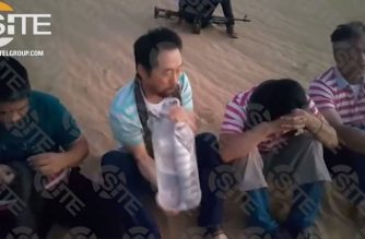 """This screen grab image taken from video released on August 1, 2018 and provided courtesy of the SITE Intelligence Group shows four hostages, one from South Korea and three from the Philippines, who are foreign employees of an engineering company in Tripoli, pictured sitting in the desert at an undisclosed location, according to SITE. Seoul said on August 2 it had deployed a warship to Libya in an apparent show of force to secure the release of a South Korean national kidnapped along with three Filipinos in the North African country. / AFP PHOTO / SITE INTELLIGENCE GROUP / Handout / -----EDITORS NOTE --- RESTRICTED TO EDITORIAL USE - MANDATORY CREDIT """"AFP PHOTO / SITE Intelligence Group"""" - NO MARKETING - NO ADVERTISING CAMPAIGNS - DISTRIBUTED AS A SERVICE TO CLIENTS"""