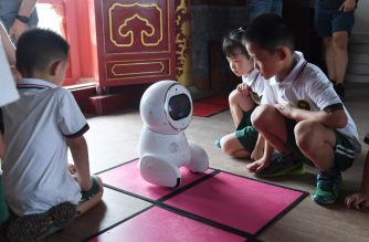 This photo taken on July 30, 2018 shows children watching a Keeko robot make its way on a path they made from square mats at the Yiswind Institute of Multicultural Education in Beijing. In China, robots are being developed to deliver groceries, provide companionship to the elderly, dispense legal advice and now, as Keeko's creators hope, join the ranks of educators. / AFP PHOTO / GREG BAKER / TO GO WITH China-science-education-robot, FEATURE by Elizabeth LAW and Danni ZHU