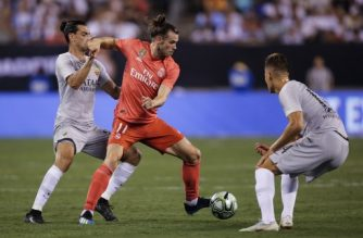 Real Madrid's Welsh forward Gareth Bale (C) fights for the ball against Roma's Argentinian defender Javier Pastore (L) and Roma's Italian midfielder Bryan Cristante (R) during their 2018 International Champions Cup at the MetLife stadium on August 07, 2018, in East Rutherford, NJ. / AFP PHOTO / EDUARDO MUNOZ ALVAREZ