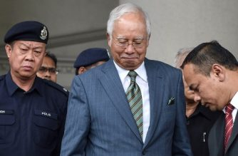 Malaysia's former prime minister Najib Razak (C) reacts as he leaves Duta court complex in Kuala Lumpur on August 8, 2018. Malaysia's former prime minister Najib Razak was hit with new charges on August 8 linked to a multi-billion-dollar financial scandal that contributed to his shock election defeat in May. / AFP PHOTO / Mohd RASFAN