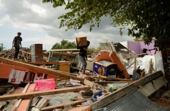 A young man salvages belongings as he climbs over debris of a collapsed house in Kayangan in northern Lombok island on August 9, 2018, following the August 5 earthquake. A strong aftershock struck Indonesia's Lombok on August 9, causing panic among evacuees sheltering after a devastating earthquake killed more than 160 on the holiday island four days earlier. / AFP PHOTO / SONNY TUMBELAKA
