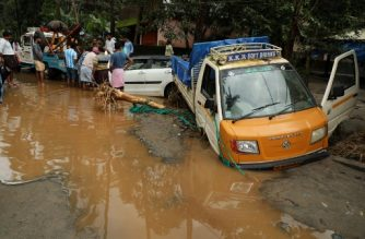 Indian people look at vehicles stuck in the mud along a flooded road at Kannappankundu in Kozhikode, in the Indian state of Kerala on August 10, 2018. Flash floods have claimed at least 27 lives in the southern Indian state of Kerala, officials said on August 10, prompting the US to advise its citizens to stay away from the tourist hotspot. / AFP PHOTO / -