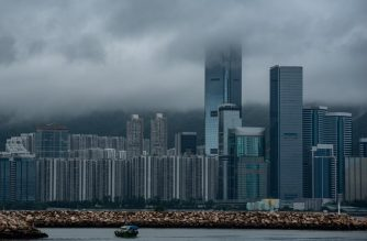 A Chinese wooden boat, known as sampan, sails through a typhoon shelter with residential buildings in Hong Kong on August 11, 2018.  / AFP PHOTO / Philip FONG