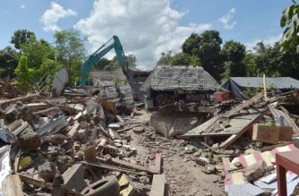 Workers take down a damaged shop with an excavator in an earthquake-hit area in Gangga on August 12, 2018. An earthquake on the Indonesian island of Lombok has killed 387 people, authorities said on August 11, adding hundreds of thousands of displaced people were still short of clean water, food and medicine nearly a week on. / AFP PHOTO / ADEK BERRY