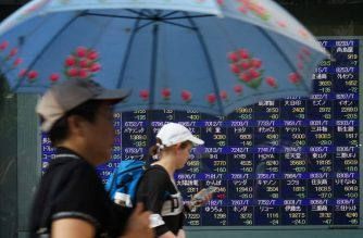 FILES: Pedestrians walk past a stock indicator board for the Tokyo Stock Exchange in Tokyo on August 13, 2018. Tokyo's benchmark Nikkei index dropped nearly two percent on August 13 as Turkey's lira plunged on tensions between Ankara and Washington, fanning fears of possible wider financial instability. / AFP PHOTO / Kazuhiro NOGI