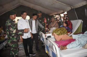 Indonesia's President Joko Widodo (2nd L) visits injured earthquake survivors at a temporary hospital in North Lombok on West Nusa Tenggara province on August 13, 2018.  The death toll from an earthquake on the Indonesian island of Lombok has topped 400, authorities said, as bodies were still being recovered from the ruins of destroyed buildings. / AFP PHOTO / STR