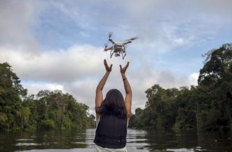 Mamiraua Institute biologist Daiane da Rosa gets back a drone during the field work of EcoDrones expedition at Mamiraua Sustainable Development Reserve in Amazonas state, Brazil, on June 27, 2018.  Drones are the new allies of investigations on Amazon river dolphins, a tool that will reduce costs and times of investigations. / AFP PHOTO / Mauro Pimentel