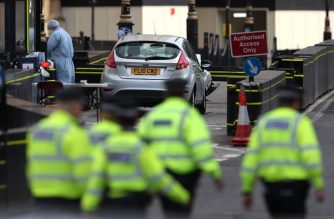 """A police forensics officer works around a silver Ford Fiesta car that was driven into a barrier at the Houses of Parliament in central London on August 14, 2018. A car crashed into barriers outside Britain's Houses of Parliament in a suspected terror attack on Tuesday, injuring a """"number of pedestrians"""" yards from where five people were killed last year. Police said they had arrested the driver, in his 20s, and were holding him on suspicion of terrorist offences. / AFP PHOTO / Daniel LEAL-OLIVAS"""