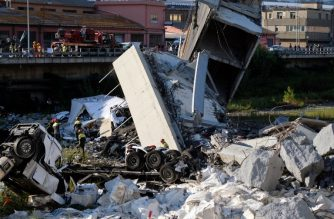 """Rescuers inspect the rubble and wreckages by the Morandi motorway bridge after a section collapsed earlier in Genoa on August 14, 2018. About 30 people were killed  when a giant motorway bridge collapsed in heavy rain in the Italian city of Genoa in what the government called an """"immense tragedy"""". The collapse, which saw a vast stretch of the A10 freeway tumble on to railway lines in the northern port city, came as the bridge was undergoing maintenance work and as the Liguria region, where Genoa is situated, experienced torrential rainfall. / AFP PHOTO / ANDREA  LEONI"""