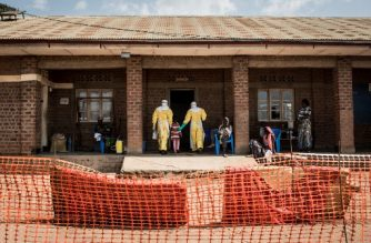Medical workers lead a young girl with suspected Ebola into the unconfirmed Ebola patients ward run by The Alliance for International Medical Action (ALIMA) on August 12, 2018 in Beni, northeastern DRC.  / AFP PHOTO / John WESSELS