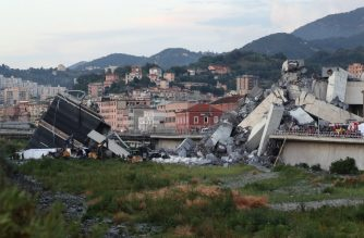 """Rescuers inspect the rubble and wreckages by the Morandi motorway bridge after a section collapsed earlier in Genoa on August 14, 2018. About 30 people were killed  when a giant motorway bridge collapsed in heavy rain in the Italian city of Genoa in what the government called an """"immense tragedy"""". The collapse, which saw a vast stretch of the A10 freeway tumble on to railway lines in the northern port city, came as the bridge was undergoing maintenance work and as the Liguria region, where Genoa is situated, experienced torrential rainfall. / AFP PHOTO / Valery HACHE"""