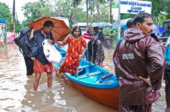 Indian volunteers and rescue personnel evacuate local residents in a boat in a residential area at Kozhikode, in the Indian state of Kerala, on August 16, 2018. The death toll from floods in India's tourist hotspot of Kerala increased to 77 on August 16, as torrential rainfall threatened new areas, officials told AFP. / AFP PHOTO / -