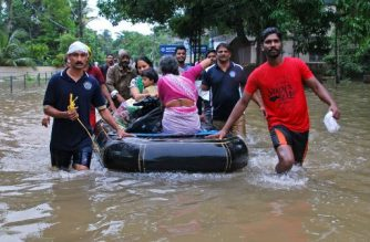 Indian volunteers and rescue personnel evacuate local residents in a boat in a residential area at Kozhikode, in the Indian state of Kerala, on August 16, 2018. / AFP PHOTO / -