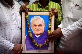Indian Bharatiya Janata Party (BJP) workers pay tribute over the portrait of  former Indian Prime Minister Atal Behari Vajpayee in Allahabad on August 16, 2018. Three-time Indian prime minister Atal Bihari Vajpayee has died, current leader Narendra Modi said on August 16 of the ailing 93-year-old who had been hospitalised. / AFP PHOTO / SANJAY KANOJIA