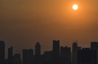 The morning sun rises past buildings and haze over the Jakarta city skyline on August 17, 2018. Indonesia is about to open the Asian Games but its traffic-clogged capital Jakarta remains shrouded in a haze of air pollution that threatens to mar the world's second-biggest multi-sport event.  / AFP PHOTO / BAY ISMOYO