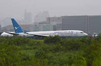 A XiamenAir Boeing 737-800 series passenger aircraft, operating as flight MF8667 from Xiamen to Manila, is seen after skidding off the runway while attempting to land in bad weather at the Manila international airport on August 17, 2018.  Some 157 passengers and eight crew were evacuated from the aircraft with no reported injuries.  / AFP PHOTO / TED ALJIBE