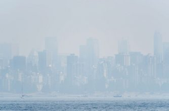 This photo shows the Vancouver skyline under heavy haze as seen from Jericho Beach on August 21, 2018. Thick smoke blanketed Vancouver on August 21, triggering warnings about dangerous particulate matter in the air and comparisons with cities in China and India ranked by the WTO as the worst polluted. It blew in more than a week ago from hundreds of wildfires burning across Canada's westernmost province of British Columbia as well as US states to the south, and according to officials was expected to linger for several more days -- marking the longest air quality alert in the picturesque coastal city's history. / AFP PHOTO / Don MacKinnon