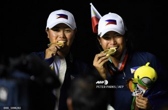 Yuka Saso (L) of the Philippines bites her gold medal as Bianca Pagdanganan (R) of the Philippies bites her bronze medal at the awards ceremony for the women's individual golf event at the 2018 Asian Games in Jakarta on August 26, 2018. / AFP PHOTO / PETER PARKS